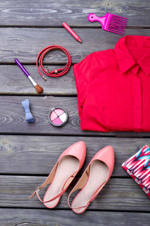 Various makeup products, shirt and shoes. Wooden desk surface background. Imagens