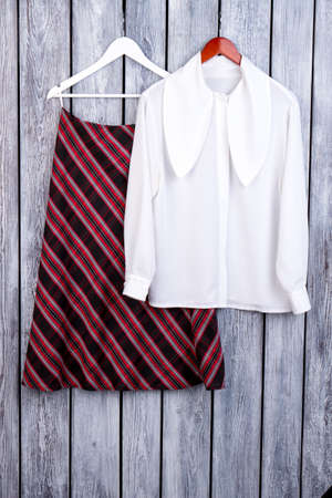 Fashionable fall womens clothing outfit. White female blouse and checkered skirt o hangers.