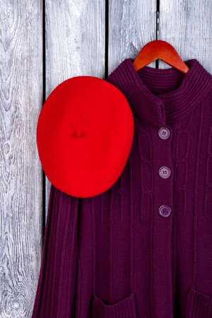 Fashionable lady winter clothes. Top view red hat and knitted coat on hanger. Dark wooden desk surface background.