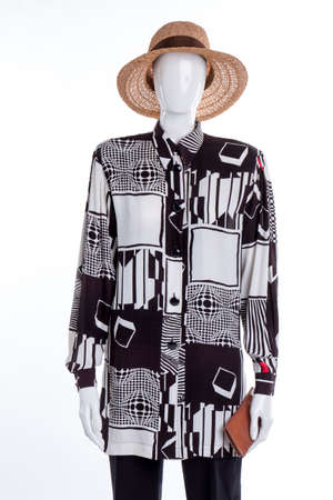 Stylish modern summer womens clothes outfit. Black and white shirt with abstract geometry print on mannequin. Straw summer hat and purse.