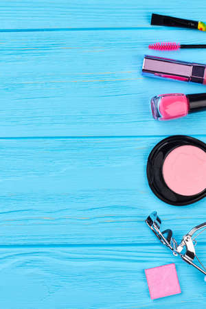 Beauty makeup essentials, copy space. Fashion color cosmetics items for beautiful makeup, blue wooden background. Feminine beauty and fashion.