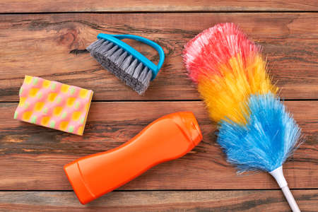 Supplies for house cleaning on wooden background. House cleaning products on wood table. Keep your home in tidiness. Stock Photo