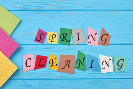 Text spring cleaning on wooden background. Kitchen cellulose napkins on blue wooden background. Time for spring clean up. Stock Photo