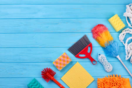House cleaning products, copy space. Flat lay house cleaning supplies on blue wooden table. Homework and housekeeping concept.