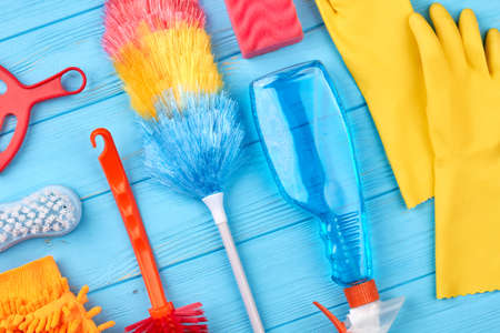 Group of objects for house cleaning. Duster broom and spray for cleaning on blue wooden background. Cleaning service concept.