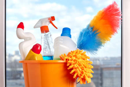 Set of cleaning products in bucket. Close up cleaning equipment on window background.