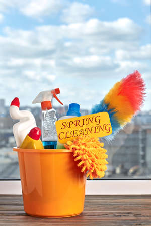Bucket with cleaning and washing items. Plastic bucket with cleaning products on window background. Stock Photo