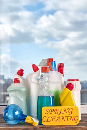 Variety of bottles with cleaning liquid. House cleaning products on window sky background. Make your home cleaner.