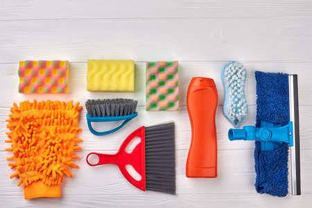 Flat lay house cleaning objects. Set of brushes and sponges for house cleaning on wooden background, space for text. Home cleaning concept.