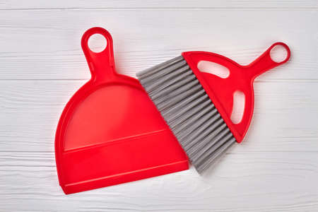 Brush and dustpan on wooden background. Set of red scoop and brush. Ready for spring cleaning. Stock Photo