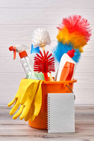 Different objects for cleaning in bucket. Colorful cleaning brushes and detergents on wooden background. Blank paper notebook. Ready for spring cleaning.