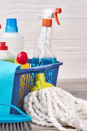 Set of detergents in plastic basket. Mop and brush for cleaning on the floor. Equipment for house work.