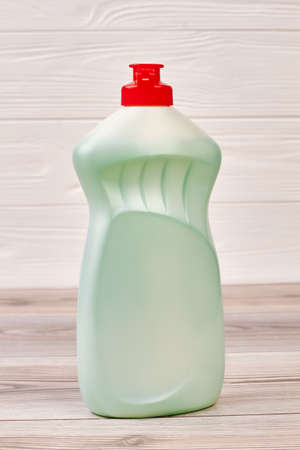 Bottle with liquid for dish washing. Green plastic detergent with red cap close up. Eco-cleaning concept. Foto de archivo