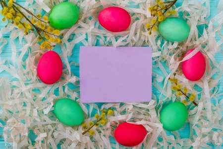 Easter composition and blank paper card. Colorful Easter eggs, pussy-willow twigs with catkins. Paper stripes and card for greeting.