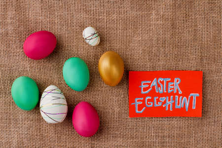 Easter egg hunt. Easter colorful eggs painted in bright colors on burlap sack background. Enjoy Easter fun.