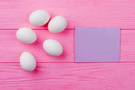 Five uncooked chicken eggs. White Easter eggs and blank paper card. Space for greeting text. Stock Photo