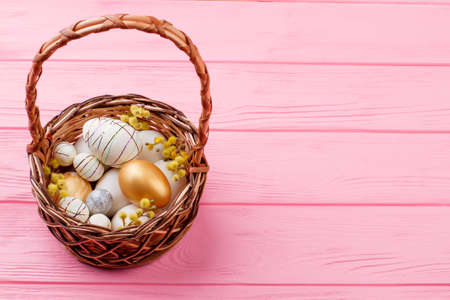 Wicker basket with Easter festive eggs. Easter eggs decorated with pussy willow twigs in woven basket, copy space.