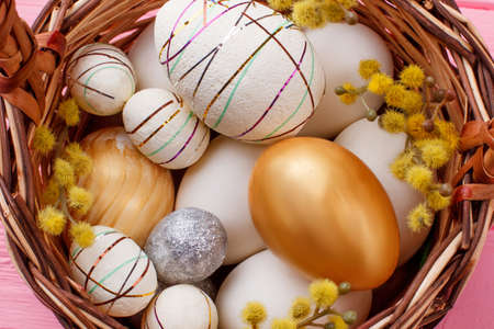 Close up festive Easter eggs in basket. Modern design Easter eggs with pussy willow in basket. Creative ways to decorate Easter eggs. Stock Photo