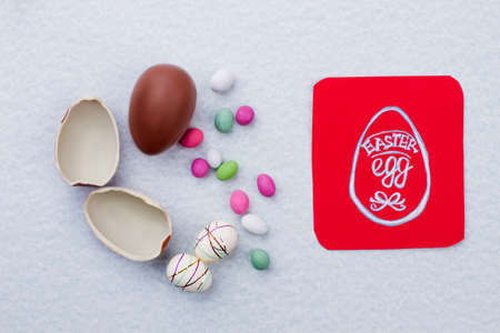 Easter background with sweets and eggs. Red paper card with picture of Easter egg. Easter greeting ideas for kids. Stock Photo