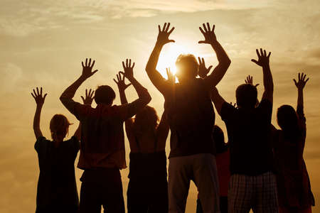 People raise hands up while live concert show, back view. Silhouette of family against evening sun background.