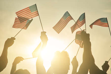 People hold up US flags during a rally in support. Patiotic people concept. Stock Photo