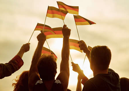 People hold german flags. Silhouette of patriotic deutsch crowd, rear view. Gloving evening sun background. Stock Photo