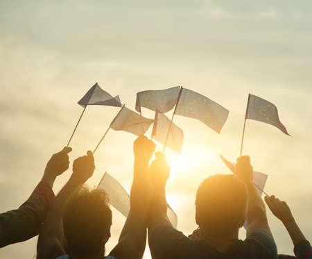 Small european union flags. Evening sunny sky background. Foto de archivo