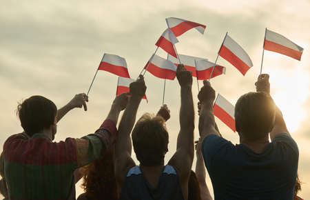 Waving poland flags. Back view silhouette of polish family.