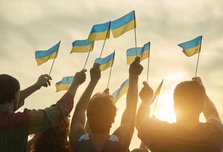 Crowd with ukrainian flags in the evening. Ukrainian revolution. Evening sunny sky background. Stock Photo