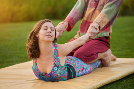 This massage pose for arms stretching. Practice of thai massage outdoor on the mat. Фото со стока