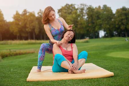Portrait of two women making thai massage. Woman sitting on mat. summer park.