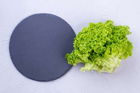 Green lettuce and natural slate board. Dark gray slate stand and fresh green lettuce salad, top view. Restaurant utensil and organic food. Stock Photo