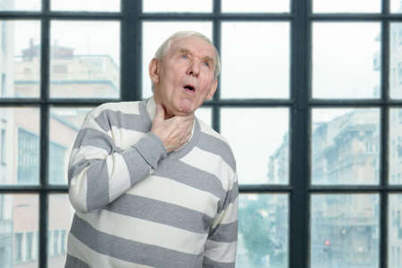 Old man is coughing. Sick senior man in windows background. Banco de Imagens