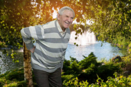 Old man with backache outdoor. Senior grandfather suffering from back pain in the park. Stock Photo