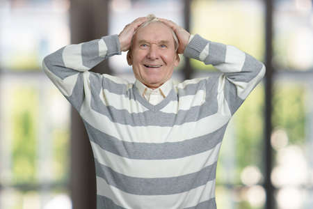 Shocked senior man touching his head. Portrait of old grandfather in windows background. Stock Photo