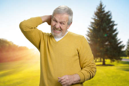 Handsome old man touching back of neck in pain. Suffering form neck pain outdoor in the morning sunny park. Stock Photo