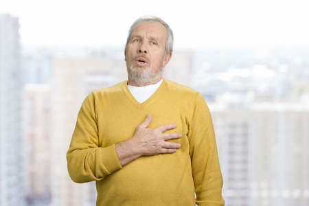 Portrait of old grandpa touching his chest. Feeling pain in heart. Urban city background.