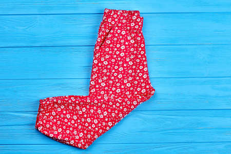 New folded colored baby girl pants. Top view of red summer trousers for small girls. Modern pockets colored pants for infant girl.