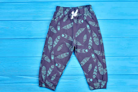 Kids feather print autumn pants. Baby boy or girl dark blue printed leggings, blue wooden background. Stylish childs wardrobe.