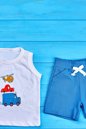 Infant boy summer casual style. Organic cotton t-shirt and shorts for baby boy on blue wooden background. Stock Photo