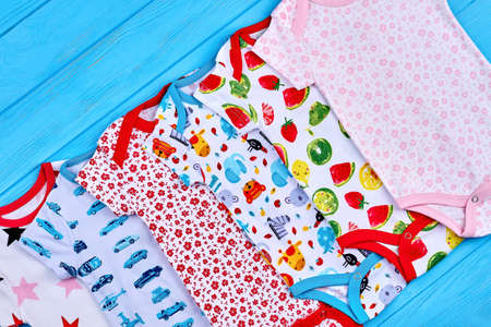 Set of printed cotton baby bodysuits. Close up of collection different organic rompers for kids. Trendy newborn outfit.