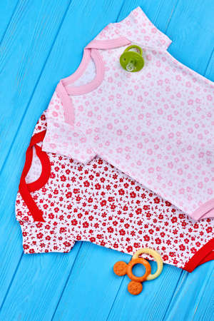 Infant baby cute summer apparel. Top view of natural printed rompers for baby-girl, accessories, wooden background.