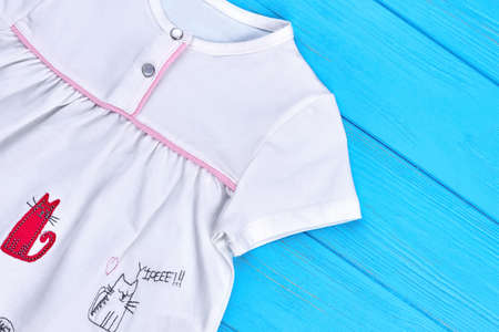 White organic cotton dress for baby-girl. Close up of baby textile gown with animal embroidery. Summer casual baby wear.