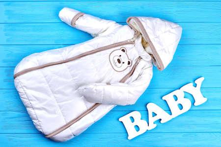 Modern design winter romper for newborn. Autumn or winter warm baby bodysuit on blue wooden background. Baby winter outdoor clothes.