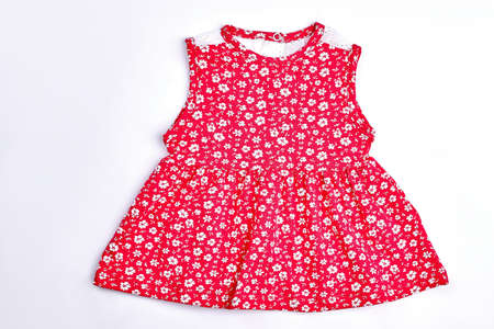 Baby-girl red flower print dress. Toddler girls red top with a pattern of smal white flowers, isolated on white background. Newborn baby girl cute sundress. Stock Photo
