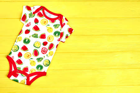 27405926e Newborn kids patterned bodysuit. Infant baby printed romper on yellow  summer background, copy space