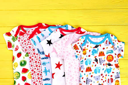 New collection of soft bodysuits for infants. Babies top quality brand rompers on yellow wooden background. Newborn kids jumpsuits on sale.