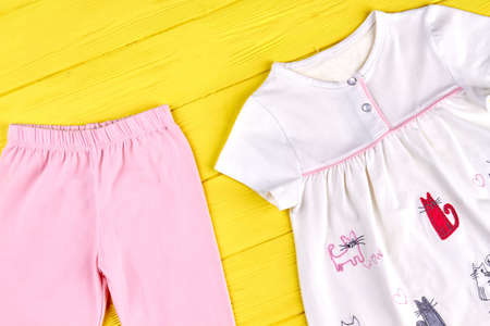 Baby-girl brand natural clothes. Infant girl beautiful sundress and pink leggings, yellow wooden background. Kids high quality outfit. Stock Photo
