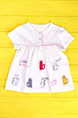 Babies white cat print dress. Infant girl short sleeve cotton dress on yellow wooden background. Kids brand outfit.