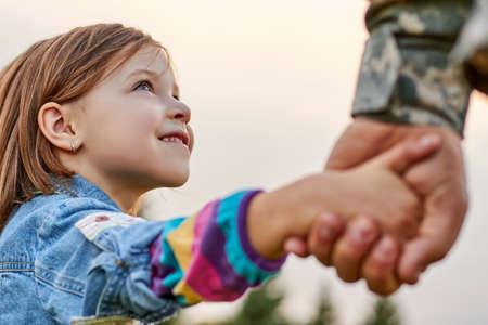 Portret klein meisje kijkt naar zijn militaire vader close-up. Mooie blik van een dochter, hand in hand. Stockfoto